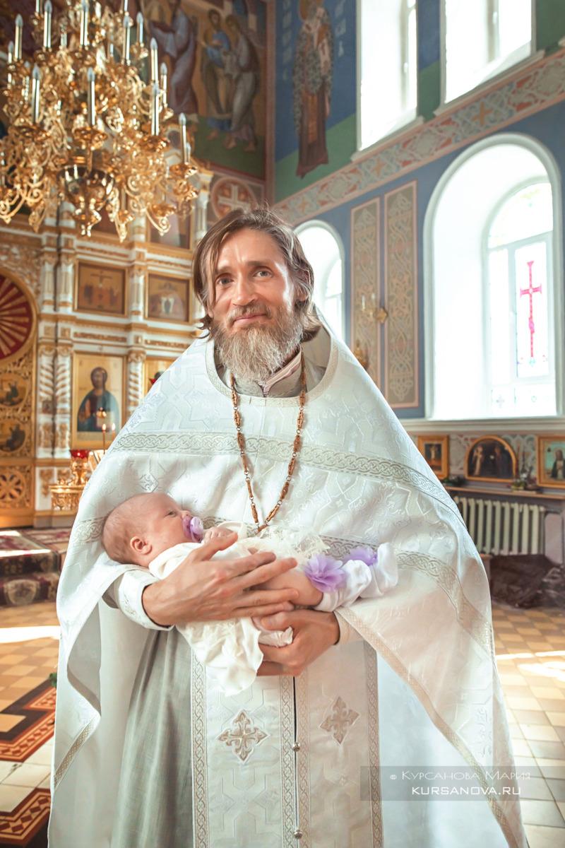 Батюшка держит ребёнка на руках после крещения