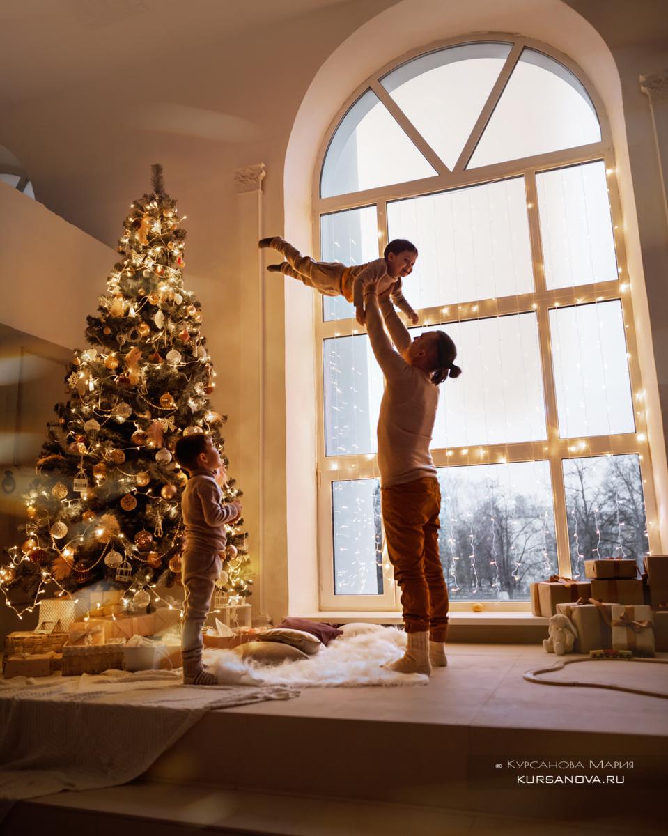 Новогодняя фотосессия всей семьей в студии, на диване около новогодней елки.