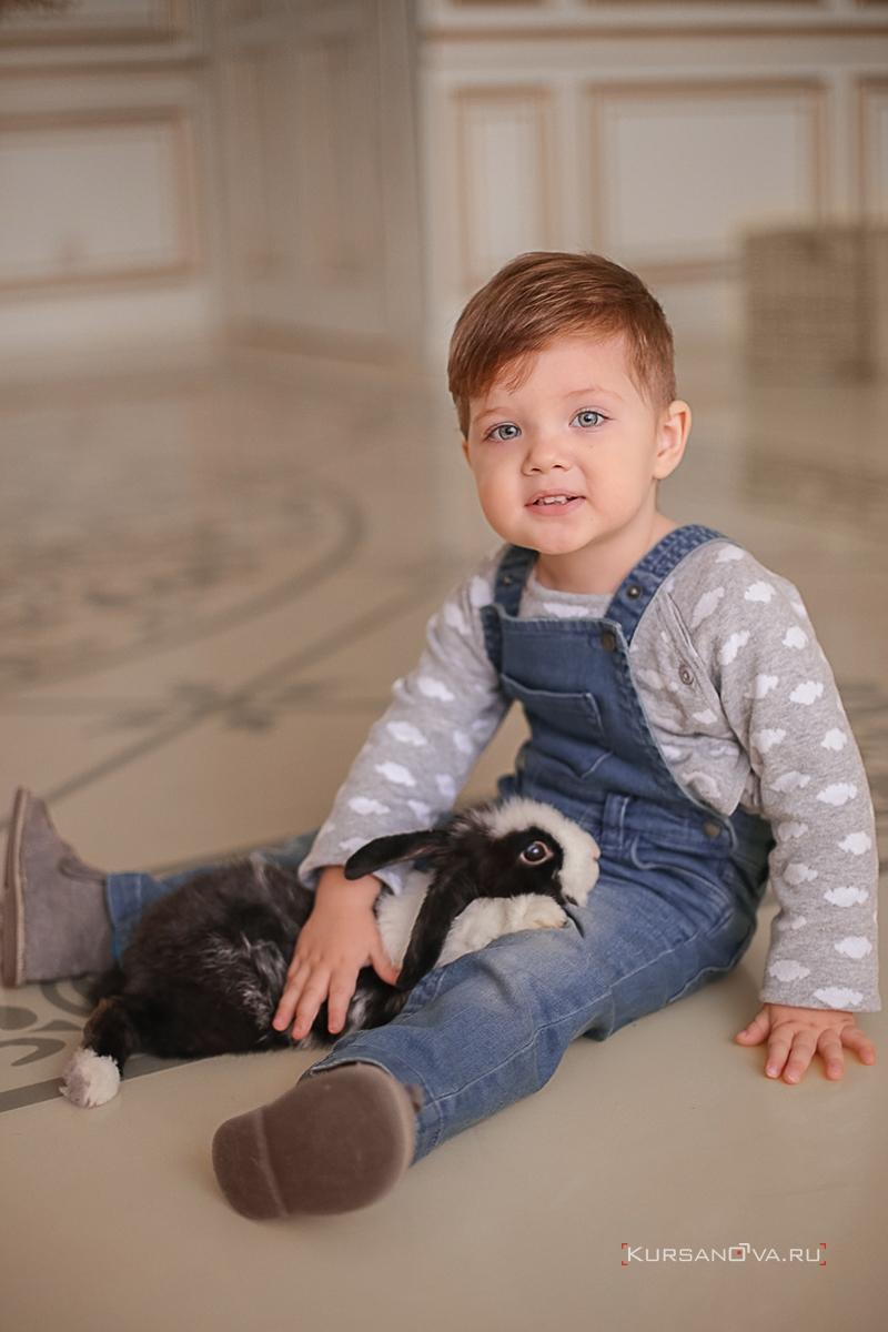Новогодняя фотосессия с маленьким ребенком в студии. Малыш сидит на полу с черно белым кроликом