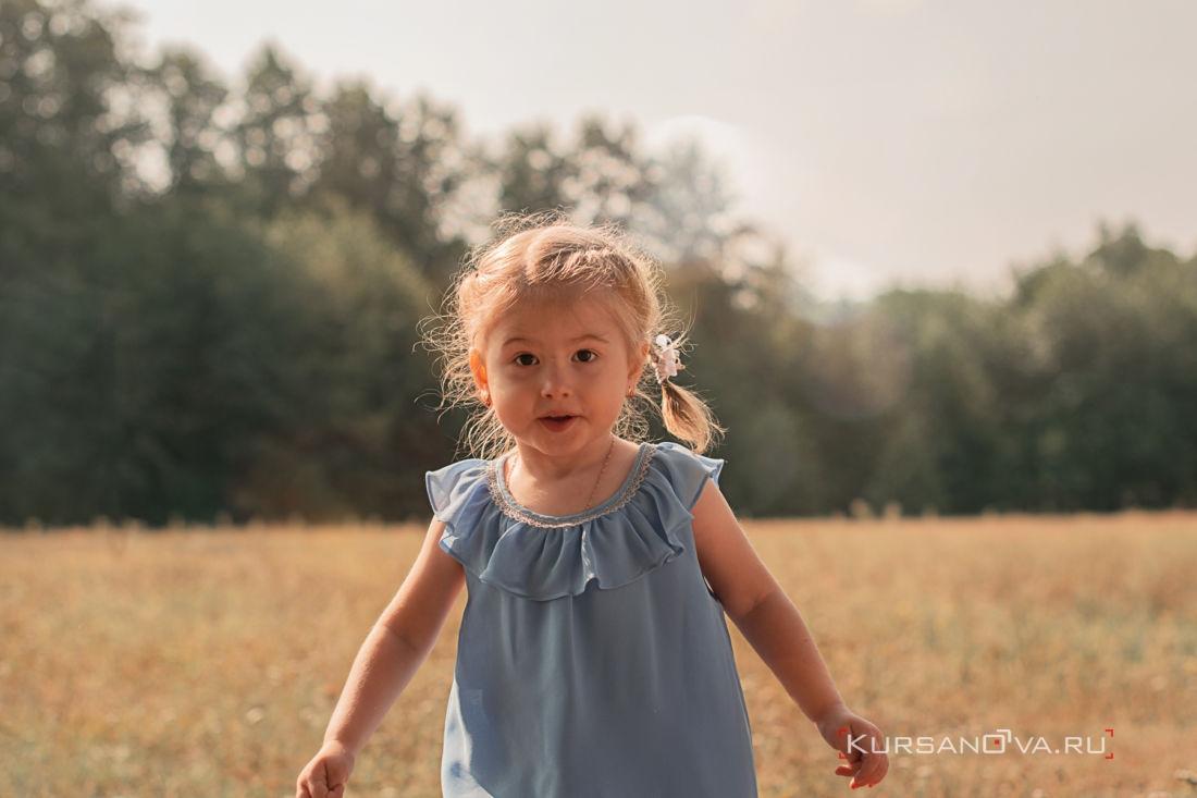 Девочка бежит по поляне на детской осенней фотосессии в Нижнем Новгороде
