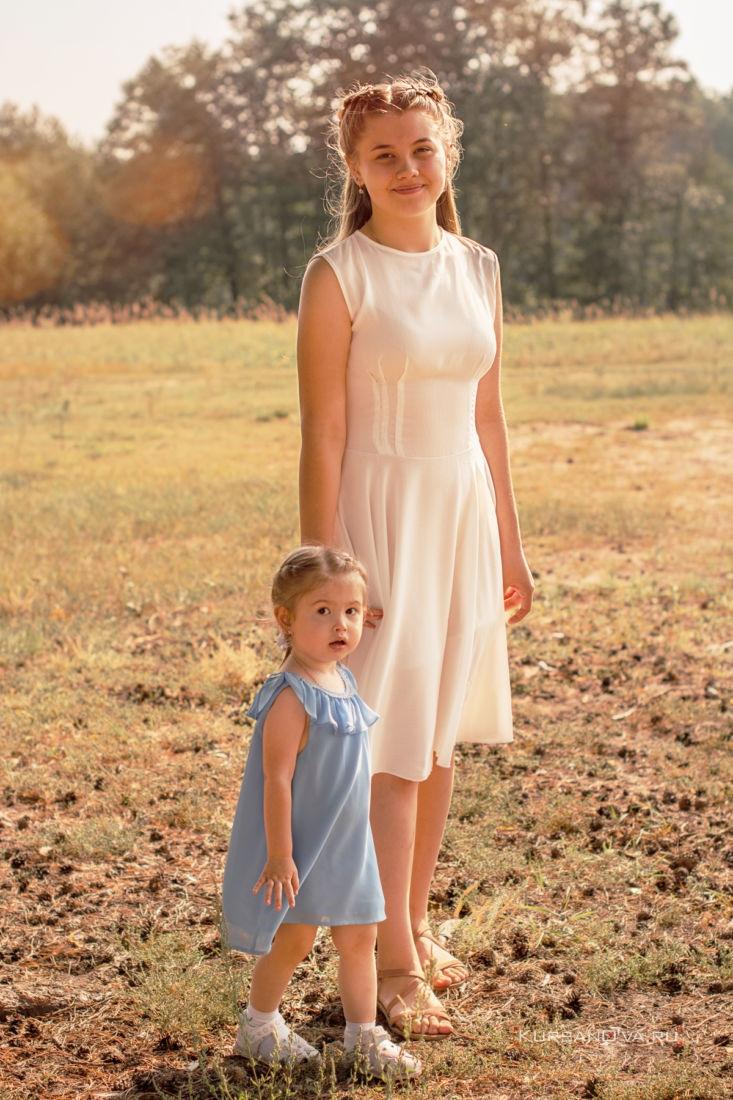 детская фотосессия на улице в Нижнем Новгороде две девочки гуляют старшая девочка держит за руку маленькую