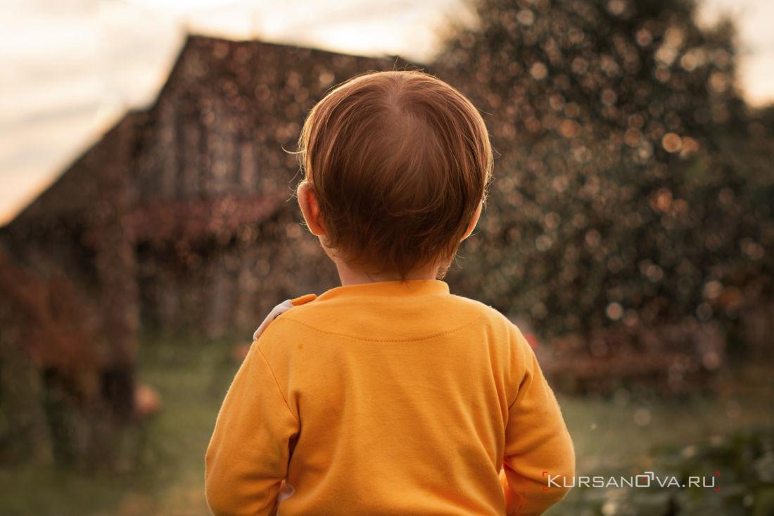 детская фотосессия на улице летом папа направил шланг в сторону и вода подсвечиваясь закатным солнышком брызгает как фантан и ребенок наблюдает за этим