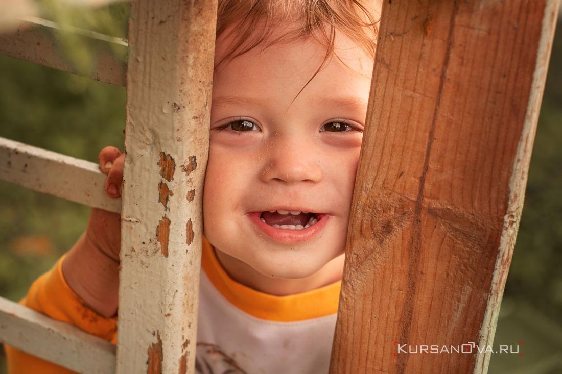 детская фотосессия летом малыш весело играет в ку ку и заразительно смеётся