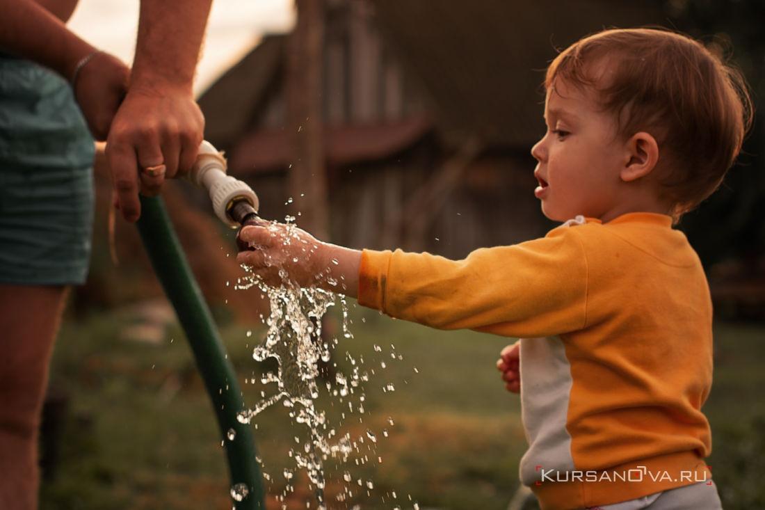 фотосессия в Нижнем Новгороде вода льется из шланга и малыш играет с водой