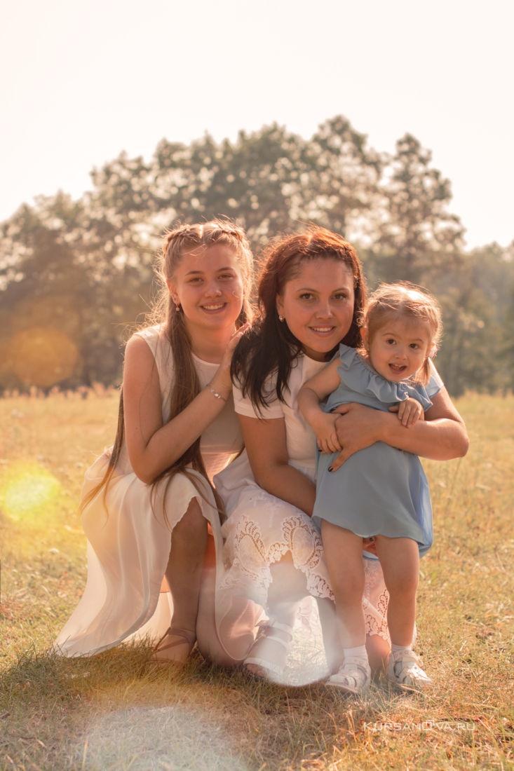 семейная фотосессия фотограф заснял маму и сестрёнок они весело обнимаются на улице теплой осенью а малышка пытается убежать