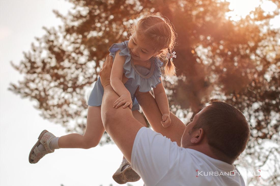 Папа играет с дочкой на семейной фотосессии в Нижнем Новгороде подкидывает малышку вверх